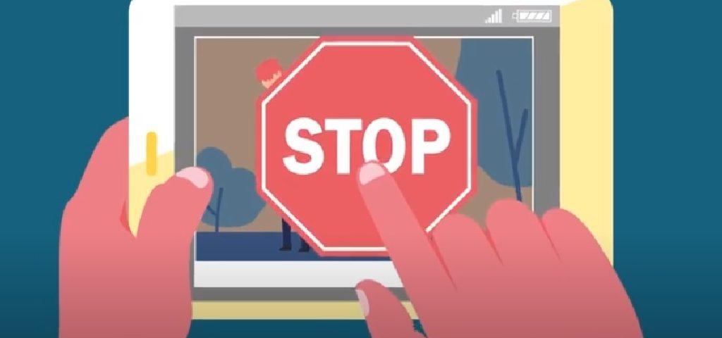 Grafika przedstawiająca ręce trzymające tablet ze znakiem drogowym STOP