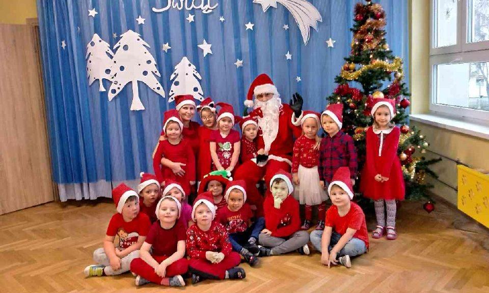 Dzieci w czerwonych strojach pozują razem z Mikołajem na tle choinki. Z tyłu niebieskie tło z białymi choinkami i białymi gwiazdkami.